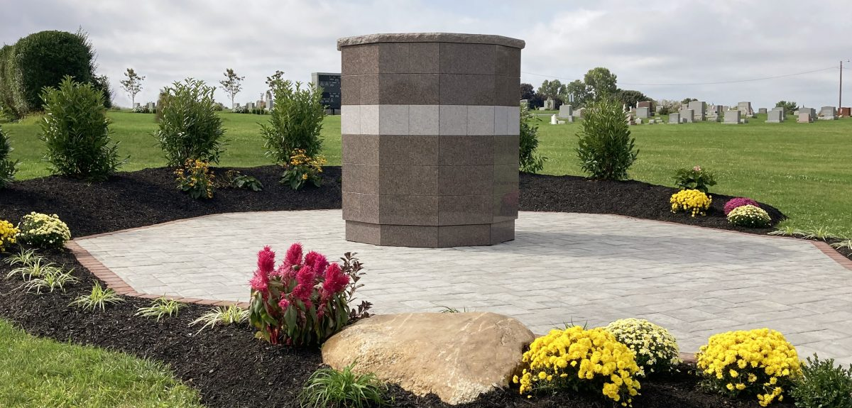 Bright planted flowers and landscaping rock surrounds a Sterling Ossuarium on a cloudy day.