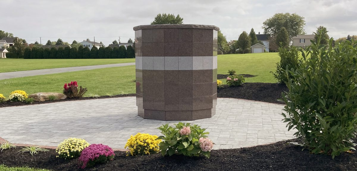 A Sterling Ossuarium sits on a circular pad of attractive pavers.