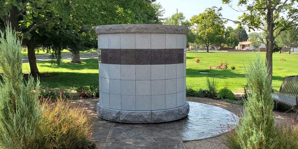 A Canterbury Ossuarium surrounded by attractive plantings and two metal benches sits atop a textured concrete pad in a cemetery.